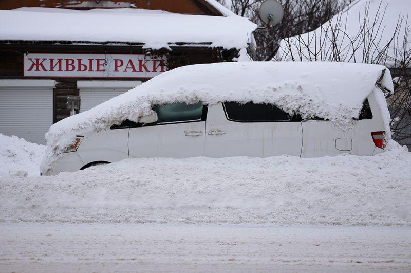 Занесенная снегом машина на улице Фадеева в Краснодаре.