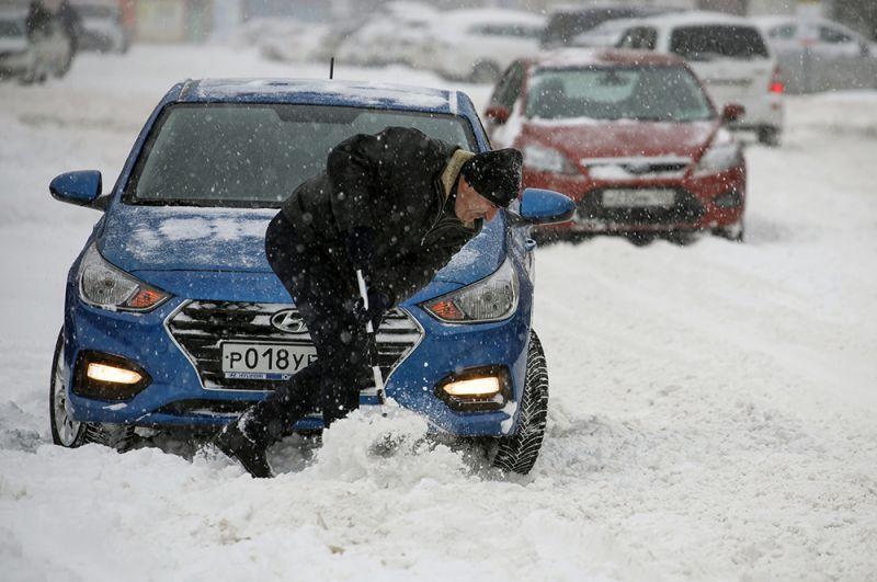 Мужчина убирает снег на улице Одесская в Краснодаре.