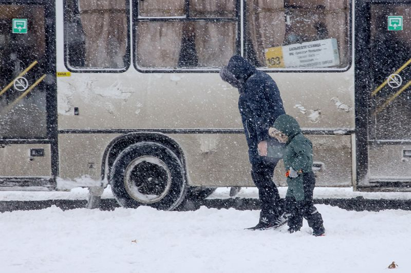 Женщина с ребенком во время снегопада на улице Краснодара.