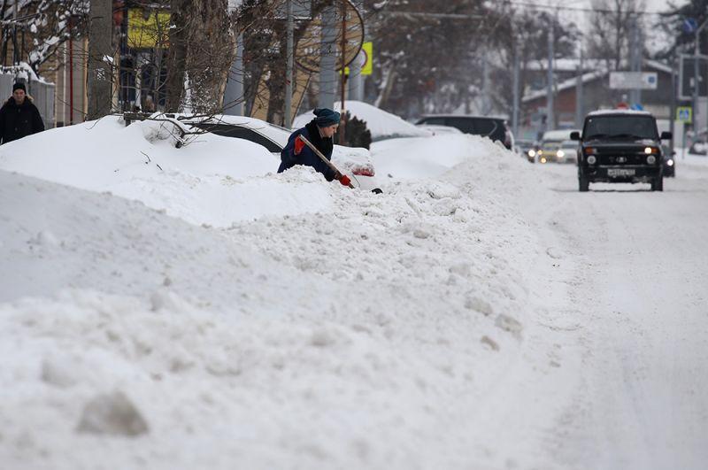 Женщина чистит снег на улице Фадеева в Краснодаре.