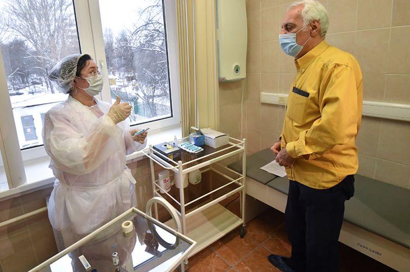 Медработник осматривает пожилого пациента перед вакцинацией от коронавируса COVID-19 вакциной «Спутник-V» в прививочном пункте городской поликлиники №2 в Северном Чертаново.