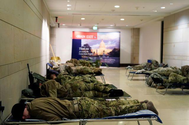 Военнослужащие Национальной гвардии США отдыхают в Центре посетителей Капитолия. Они прибыли туда, чтобы обезопасить церемонию инаугурации от возможных беспорядков.