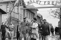 Выжившие в Освенциме покидают лагерь. Над ними – немецкий лозунг «Arbeit macht frei» («Работа делает человека свободным»), февраль 1945 г.