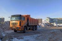 В Оренбурге два самосвала сваливали грязный снег за жилым комплексом.