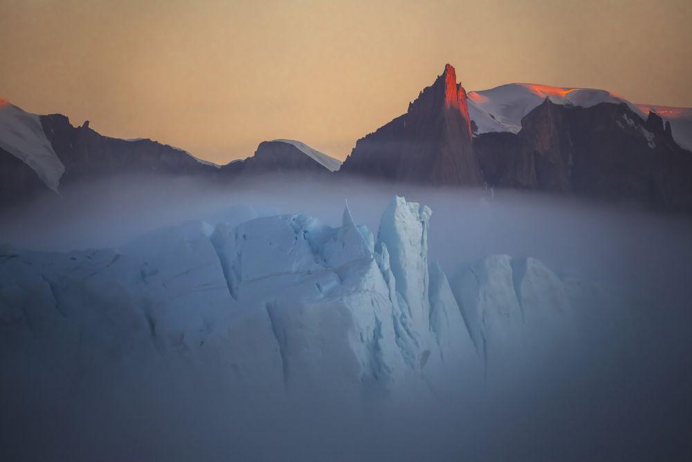 А на этом снимке фотограф запечатлел очень редкое природное явление — туман над айсбергом в Гренландии.