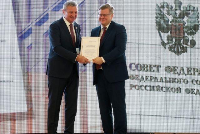 Сенатор Сергей Муратов вручает награду исполнительному директору ПАО «Курганмашзавод» Петру Тюкову.