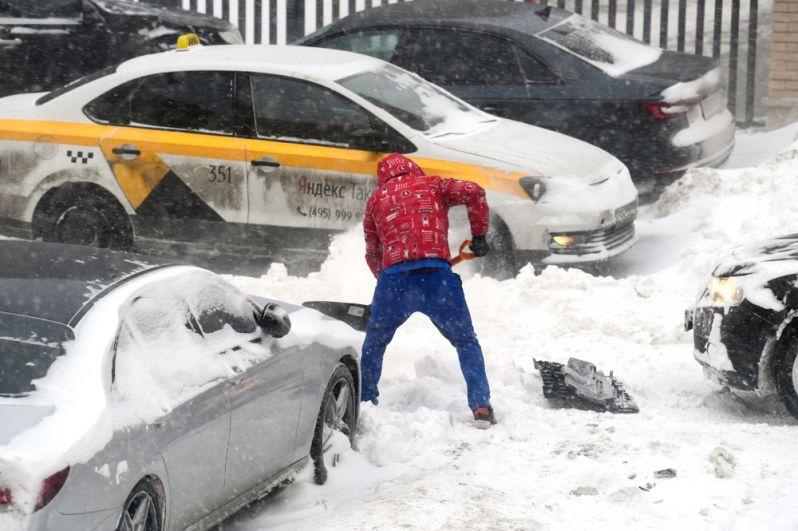Мужчина откапывает из сугроба свою машину во дворе жилого дома в Москве.