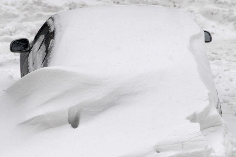 Засыпанный снегом автомобиль во дворе жилого дома в Москве.