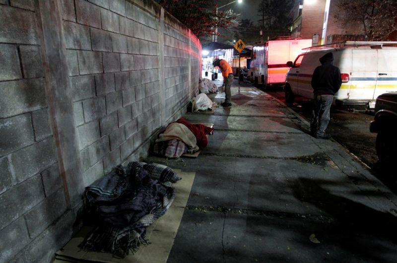 Монтеррей, Мексика. Сотрудники гражданской обороны проверяют спящих на улице людей во время аномальных холодов.