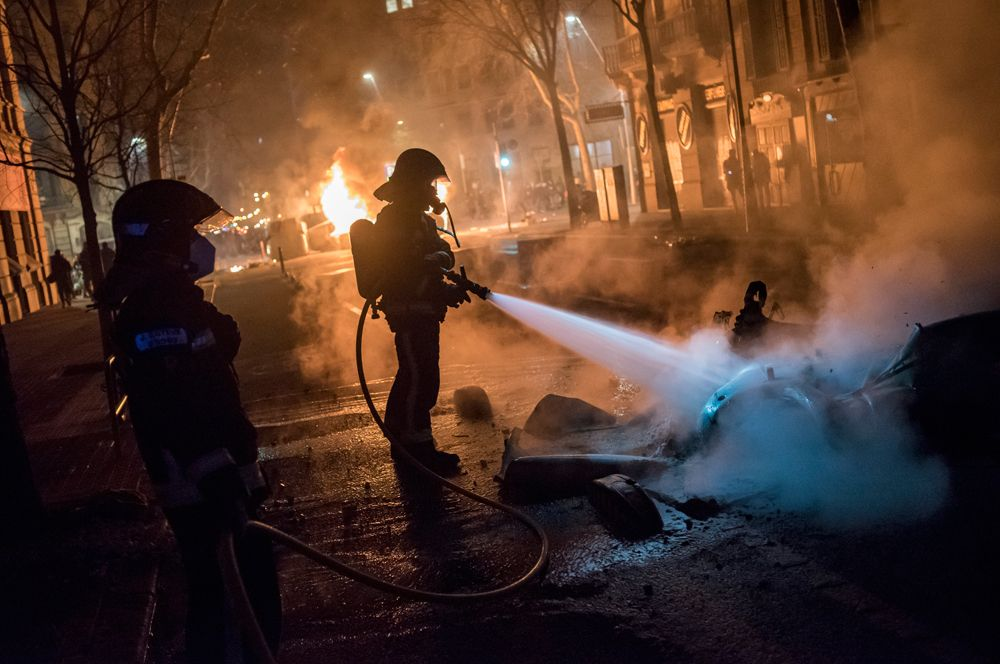 Сотрудники пожарной службы тушат горящие скутеры на одной из улиц Барселоны.