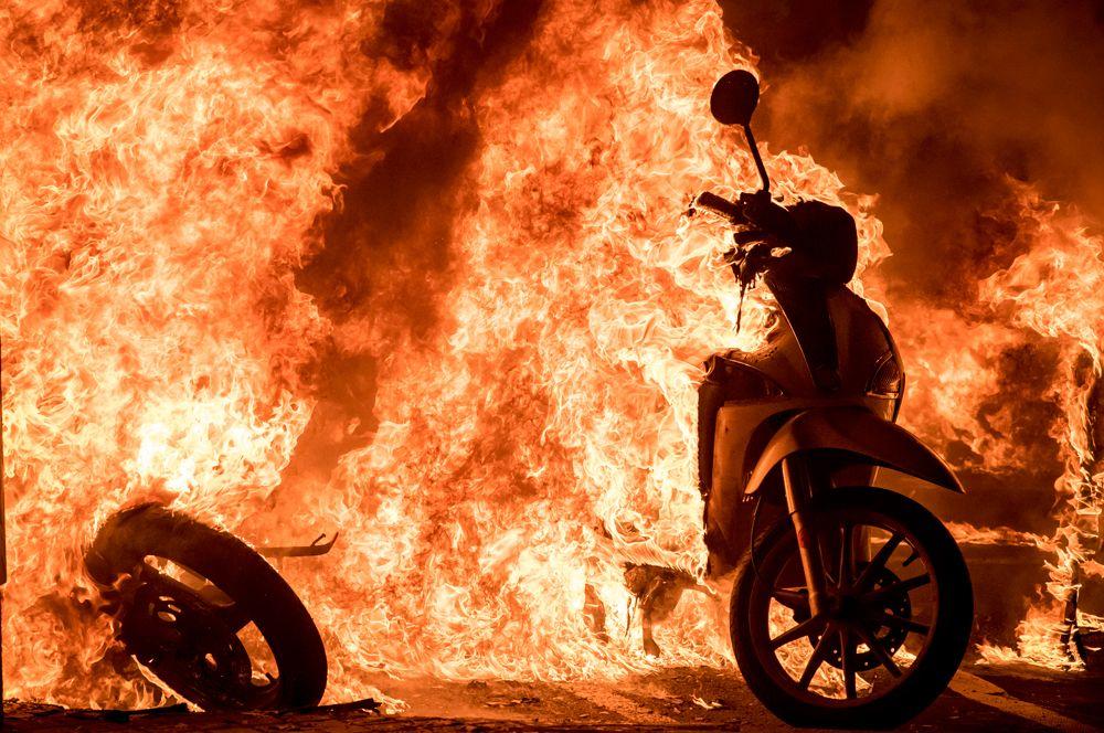 Горящие скутеры на одной из улиц Барселоны, где проходит акция протеста в поддержку рэпера Пабло Аселя.