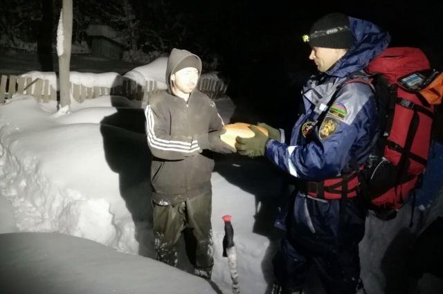 Спасатели передают хлеб жителям поселка, к которому сейчас не добраться на транспорте.