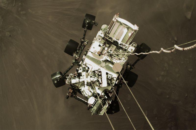 Планетоход Perseverance опускается на поверхность планеты. Снимок сделан камерой, установленной на борту спускаемой ступени.