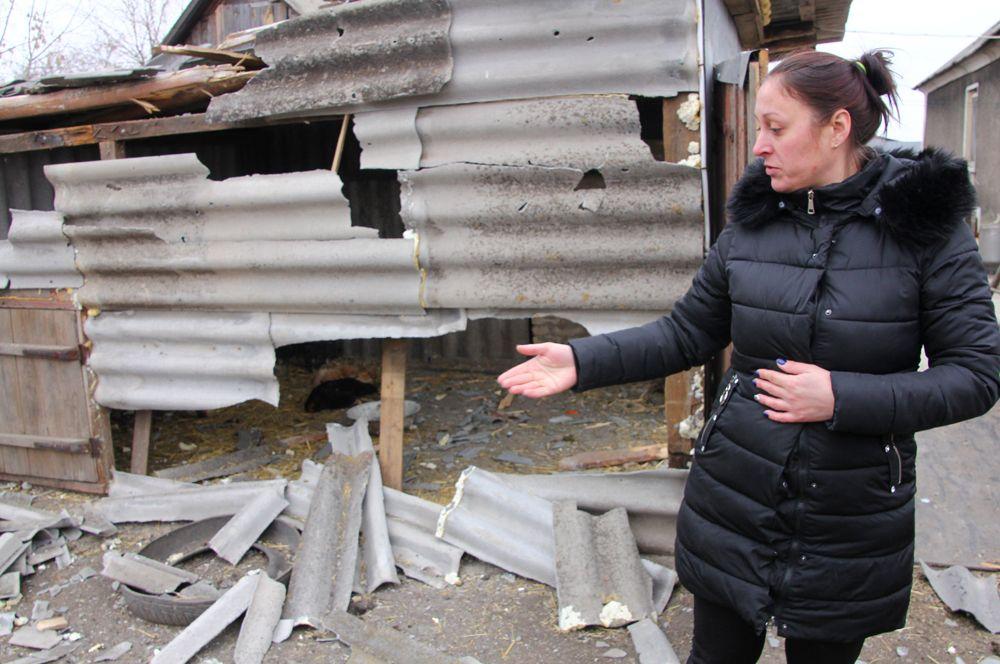 Жительница поселка Еленовка показывает последствия артобстрела.