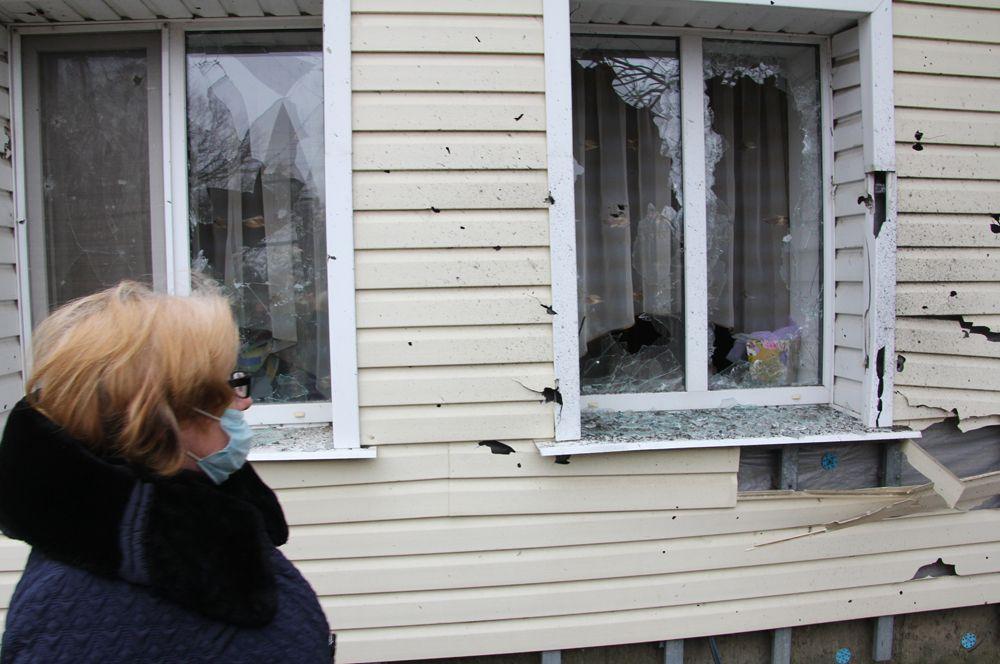 Жительница поселка Еленовка осматривает свой дом, поврежденный артобстрелом.