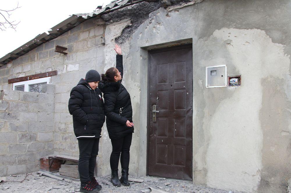 Жительница поселка Еленовка показывает свой дом, поврежденный артобстрелом.