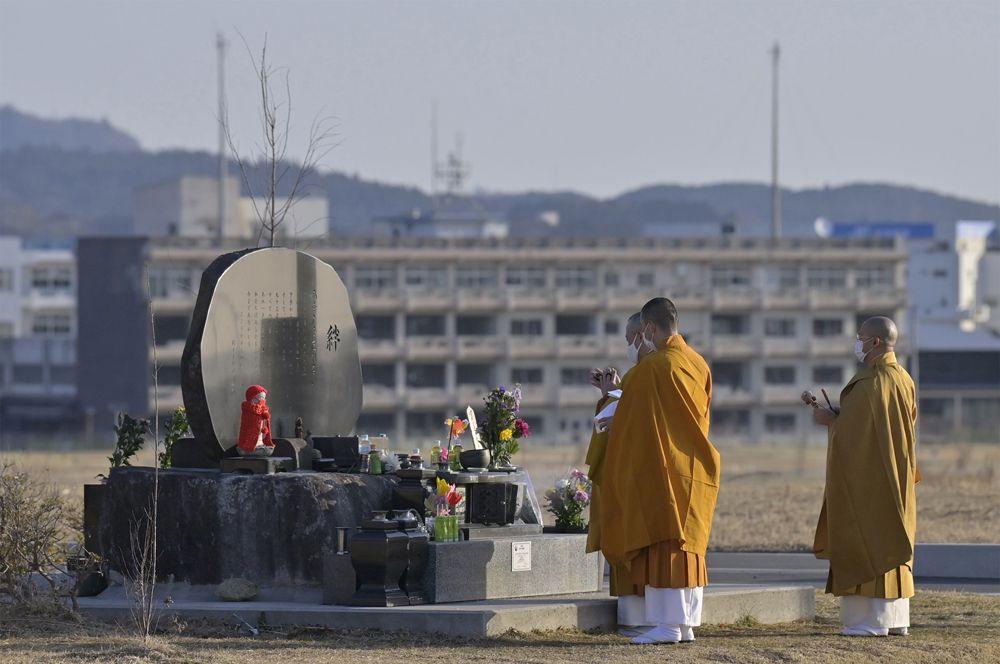Буддийские монахи молятся перед мемориалом, воздвигнутым в память о жертвах землетрясения и цунами 11 марта 2011 года на фоне разрушенного цунами здания средней школы в Кесеннуме, на северо-востоке Японии,