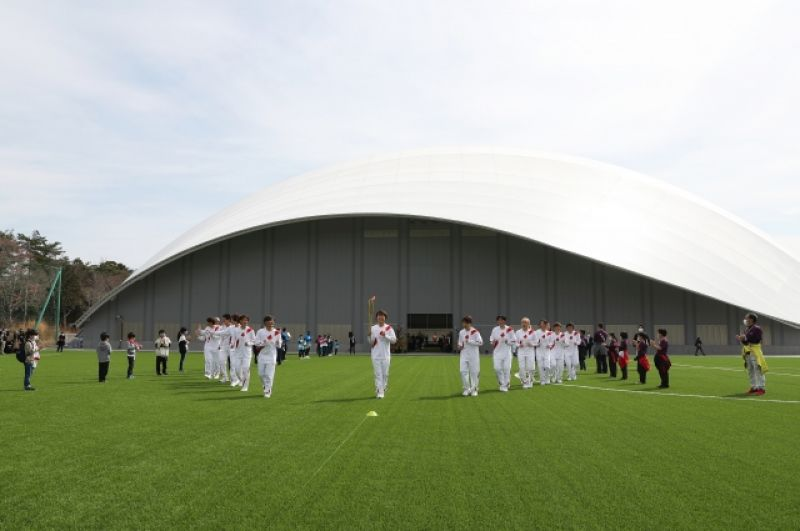 Бывшие члены женской национальной сборной Японии по футболу «Надесико Япония» бегут в качестве факелоносцев в Национальном тренировочном центре J-Village в Футаба, Фукусима, Япония.