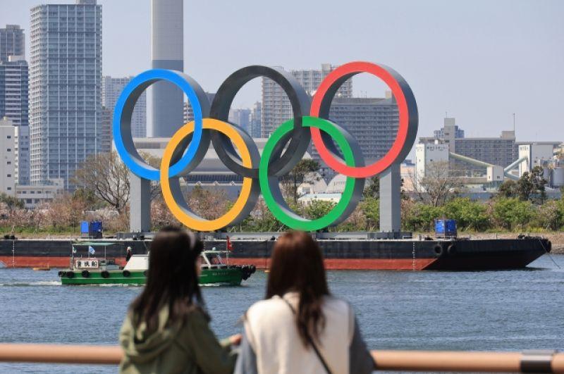 Жительницы Токио смотрят на олимпийские кольца с набережной Дайба.