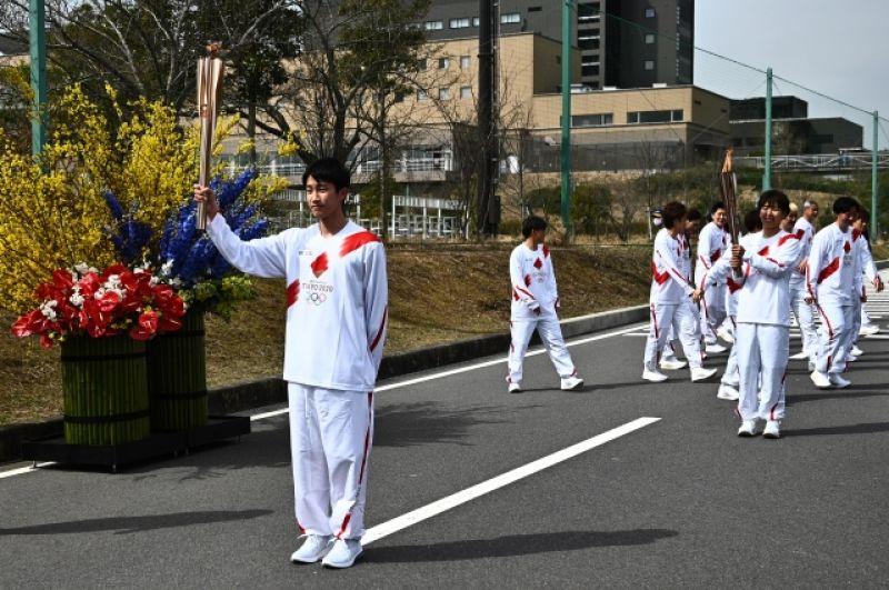 Японский школьник Асато Овада держит факел во время эстафеты.