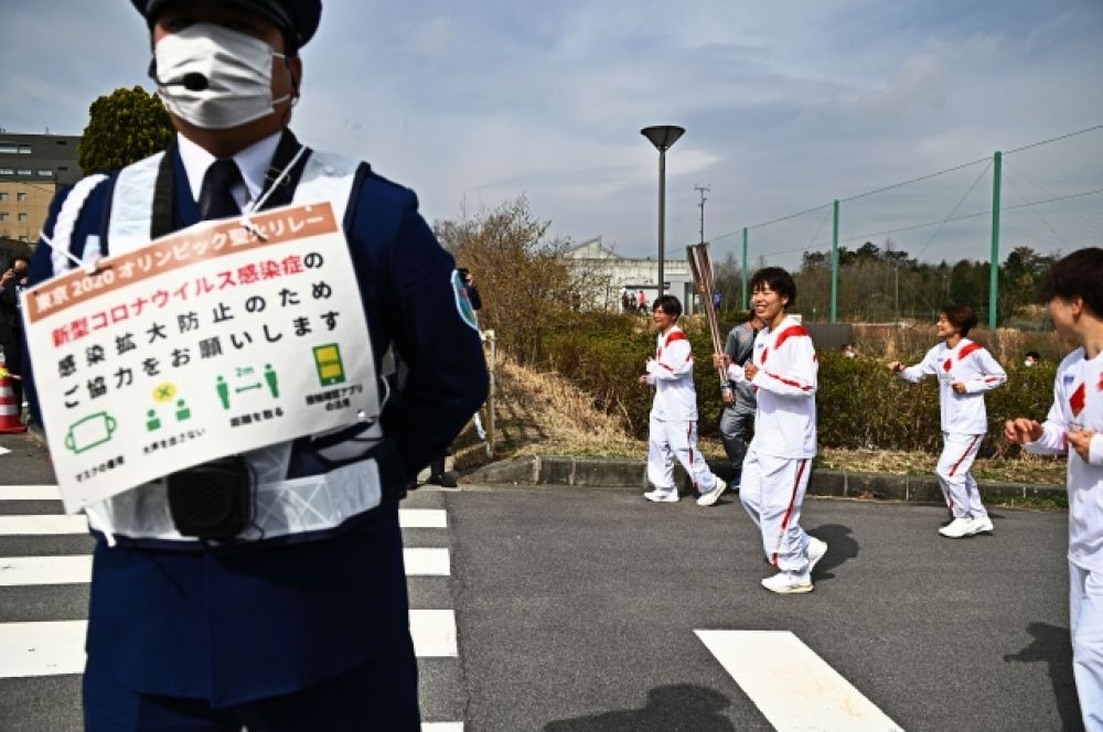 Бывшая член женской сборной Японии по футболу Ивашимидзу Азуса (3-я справа) несет олимпийский факел во время эстафеты на Олимпийских играх в Токио в Футабе, Фукусима.