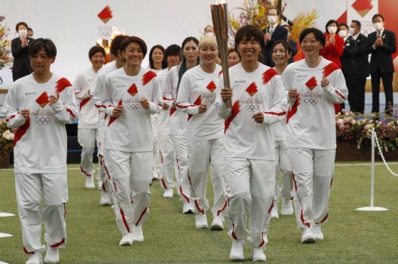 Бывшие члены женской национальной сборной Японии «Надэсико Япония» несут факел в первый день эстафеты Олимпийского огня в Токио-2020.