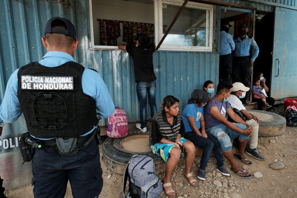 Полицейский Гондураса проверяет документы мигрантов, идущих в США, на пограничном переходе с Гватемалой.