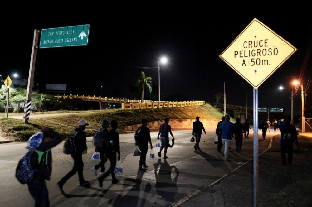 Мигранты из Гондураса идут по ночной улице в Сан-Педро-Сула.