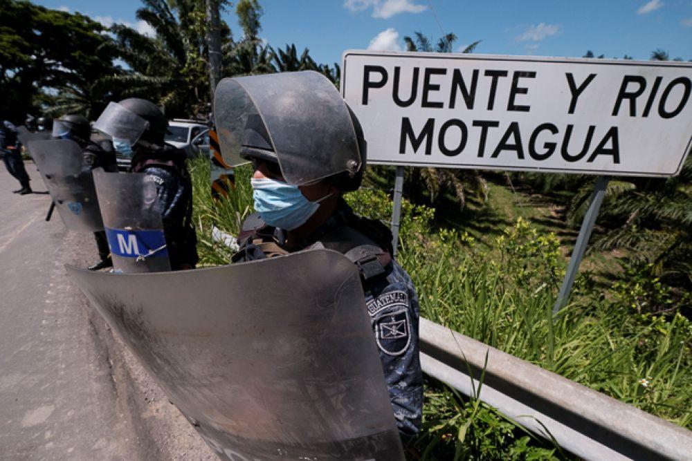 Офицеры военной полиции Гватемалы стоят вдоль моста через реку Мотагуа, чтобы сдерживать гондурасцев, участников каравана мигрантов, идущих в США.