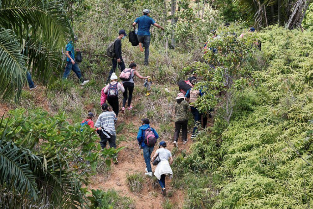 Мигранты из Гондураса стремятся нелегально перейти границу недалеко от пограничного пункта пропуска Коринто с Гватемалой, чтобы избежать полицейского контрольно-пропускного пункта.