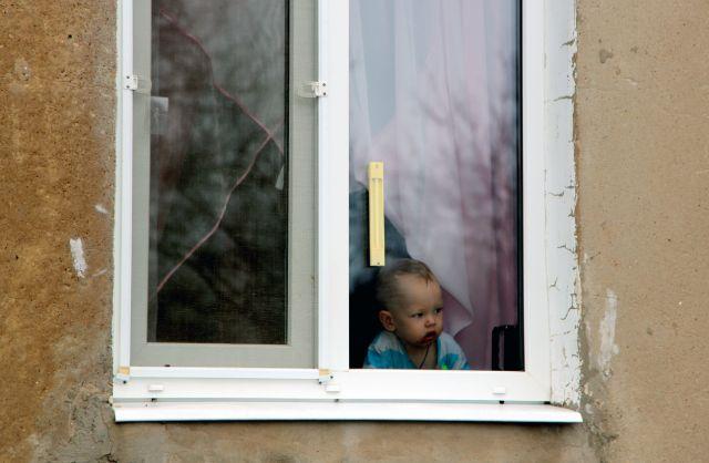 Маленький ребенок в окне одного из домов поселка шахты «Глубокая» в Горловке, который находится рядом с линией соприкосновения в Донецкой народной республике и постоянно подвергается обстрелам.