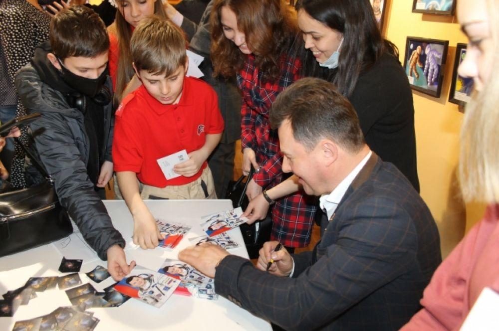 Среди желающих взять автограф у космонавта были взрослые и дети.