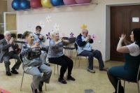Подопечные центра социального обслуживания делают гимнастику.