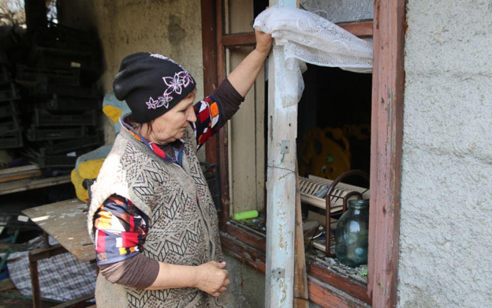 Местная жительница из села Васильевка Донецкой области показывает повреждение в своем доме, пострадавшем в результате обстрела.