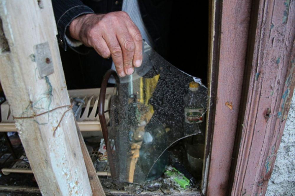 Местный житель из села Васильевка Донецкой области держит кусок разбитого стекла из разбитого окна жилого дома, пострадавшего в результате обстрела.