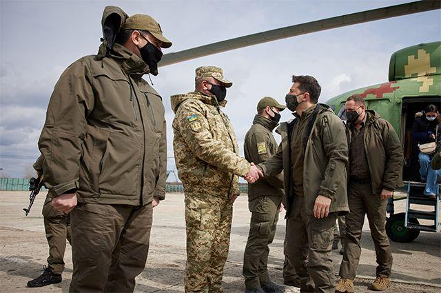 Президент Украины Владимир Зеленский пожимает руку военнослужащему во время рабочей поездки на линию фронта 8 апреля 2021 года.