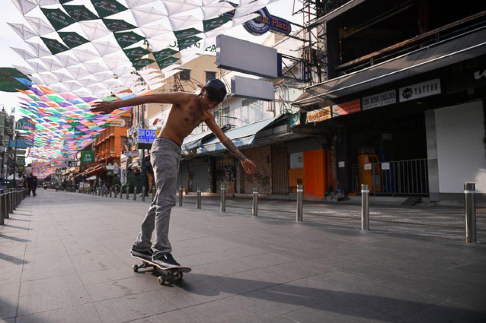 Работник ресторана катается скейтборде на почти пустой улице Каосан во время праздника.