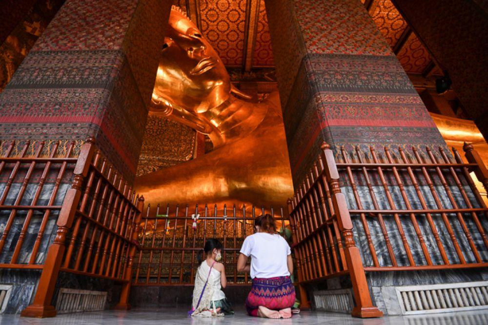 Люди в защитных масках молятся перед статуей Будды.