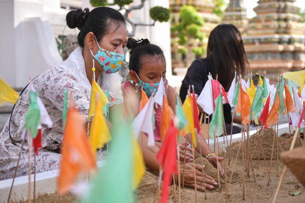 Люди в защитных масках строят песочные пагоды.