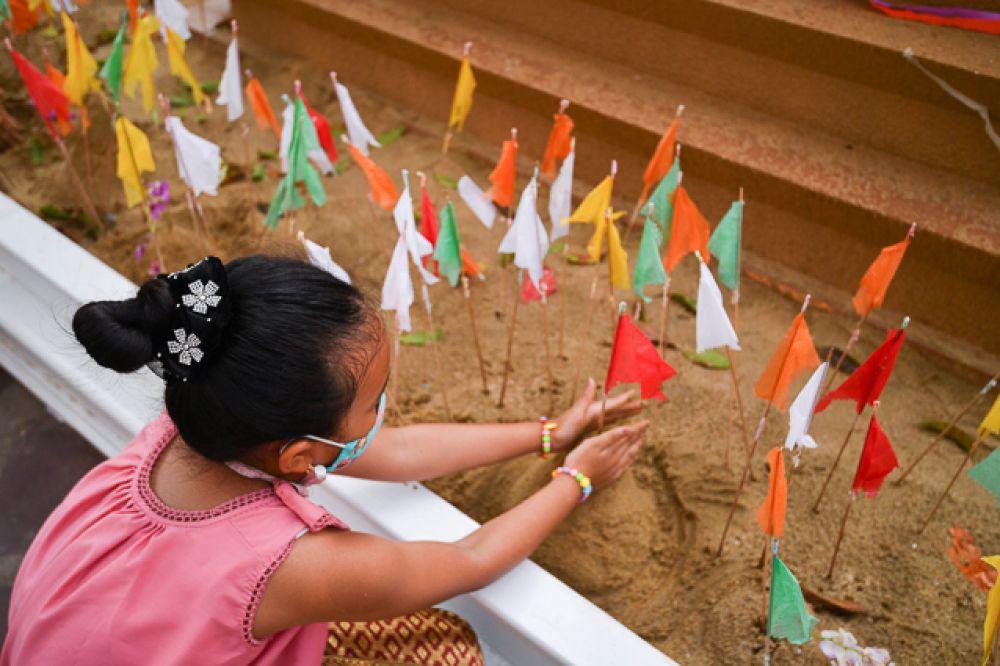 Девочка строит пагоду (буддистский храм) из песка.