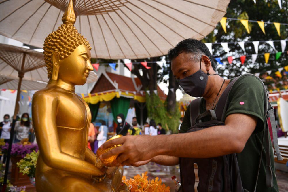 Мужчина в защитной маске поливает водой статую Будды.