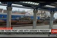 На видео видно, что железнодорожные платформы с танками следуют на фоне пассажирских вагонов в сине-желтой украинской расцветке. Кадр из видео CNN.