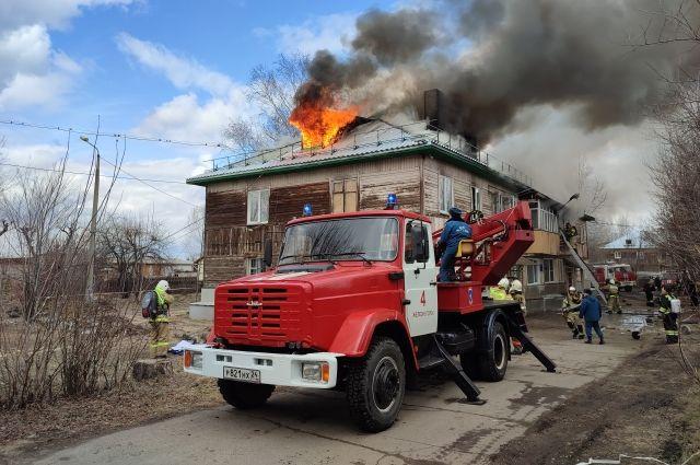 Пламя врывается из чердачного окна наружу.