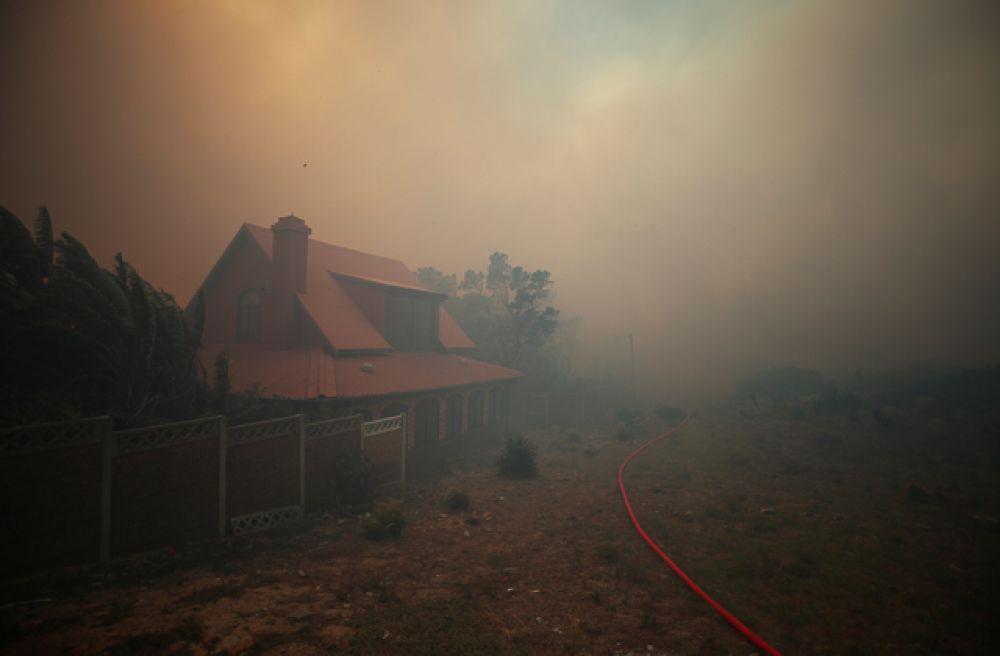 Виден окутанный дымом дом, когда пожарные сражаются, чтобы сдержать огонь.