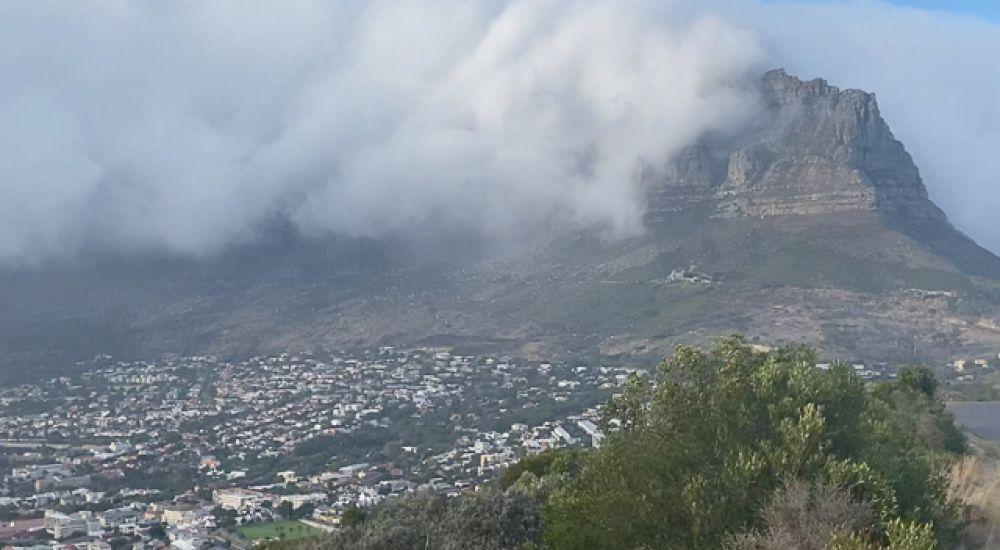 Облако дыма, вызванное лесным пожаром, видно с Сигнальным холмом над районом Сити-Боул в Кейптауне.