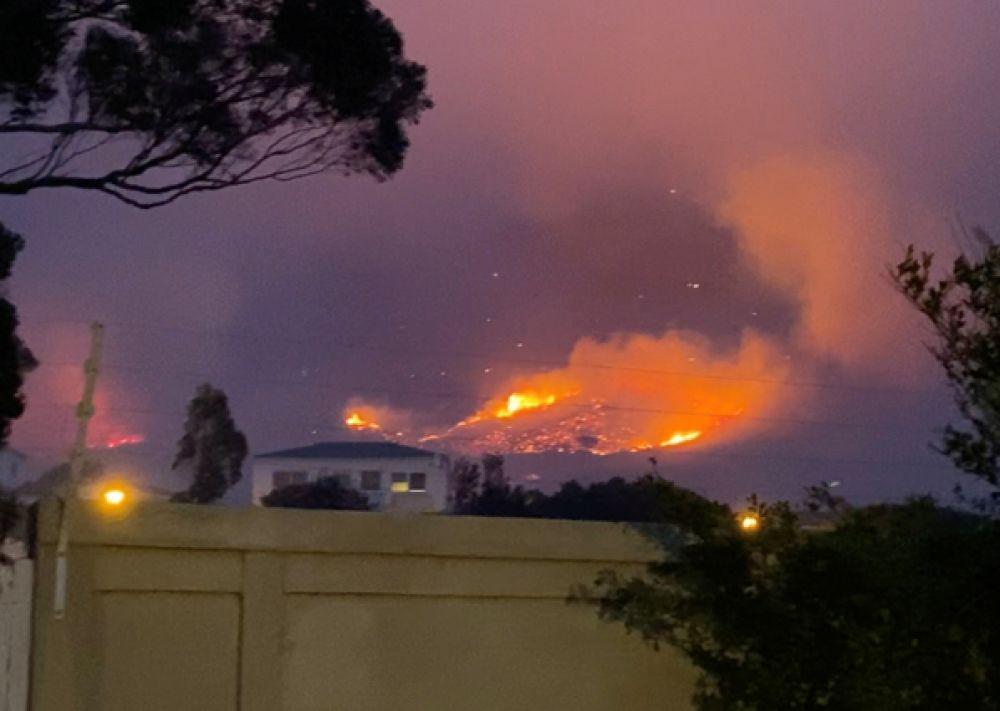 Дым и пламя от лесного пожара видны из пригорода Вредехук в Кейптауне.