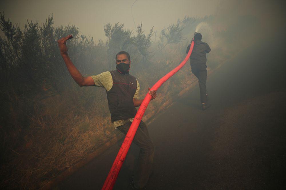 Жители и добровольцы сражаются, чтобы сдержать пожар, раздуваемый сильным ветром.