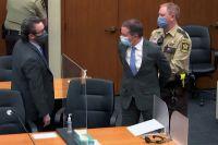 Бывшего офицера полиции Миннеаполиса Дерека Човена уводят внаручниках мимо своего адвоката Эрика Нельсона после того, как присяжные признали его виновным повсем пунктам обвинения.