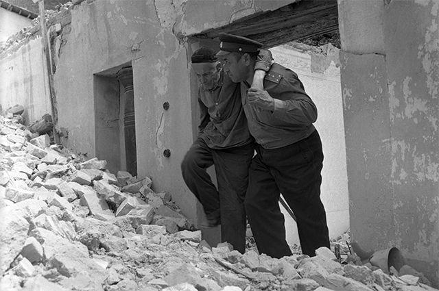 Узбекская ССР. Ликвидация последствий землетрясения в Ташкенте 26 апреля 1966 года. Капитан милиции Шамахсуд Шарахнедов помогает выйти из разрушенного дома раненому жителю.