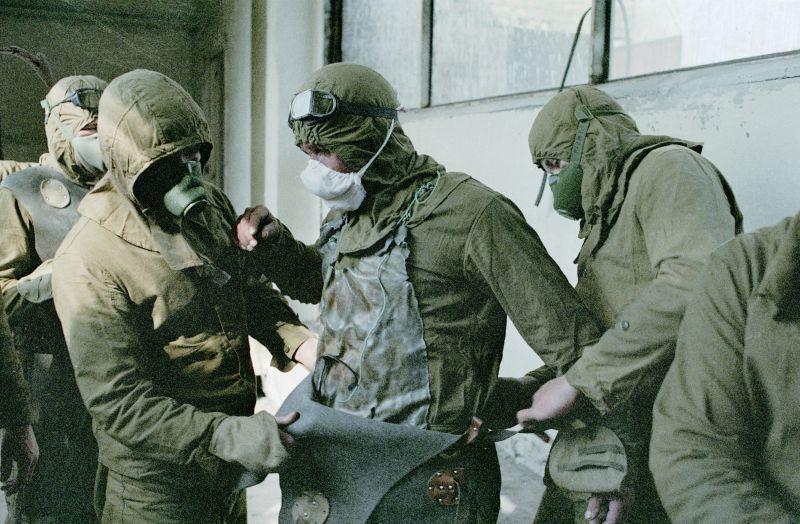 Люди одеваются в защитные костюмы перед расчисткой кровли повреждённого реактора, 14 августа 1986 года